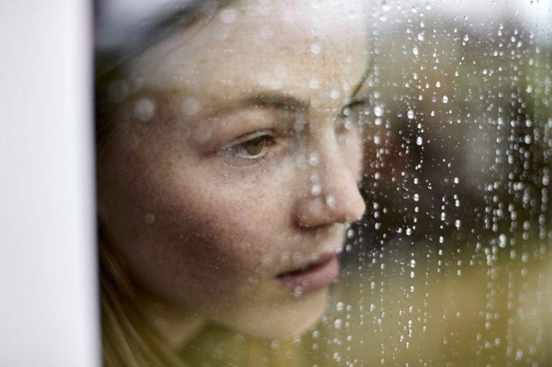 woman at window looking sad