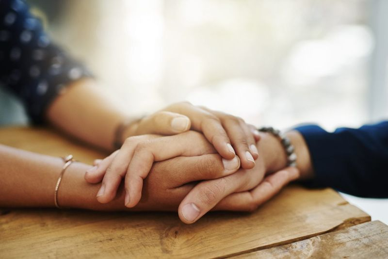 two people holding hands support