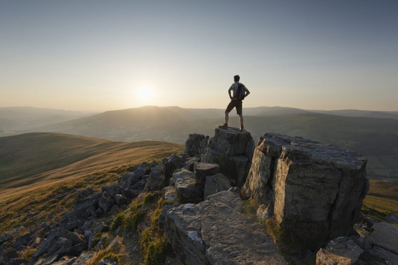 man standing on mountain top with sunset