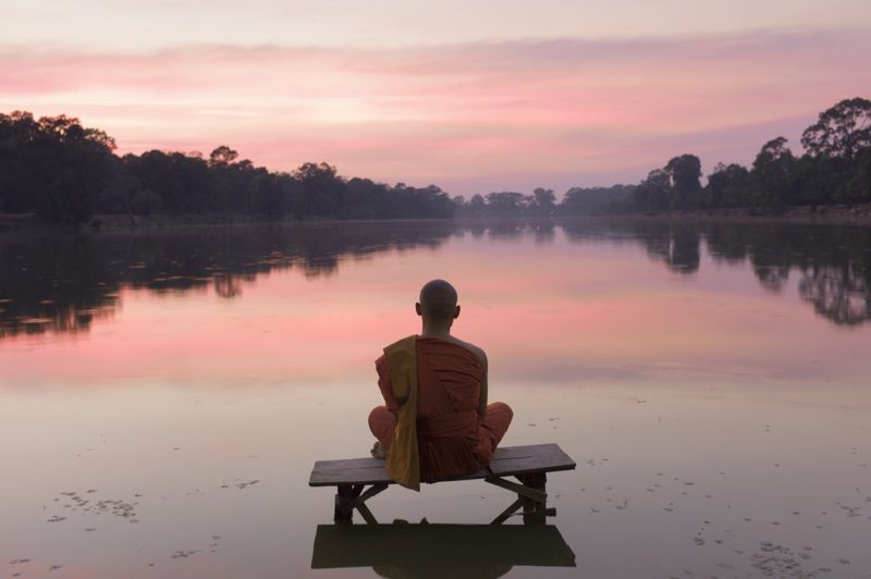 wise monk sitting by water