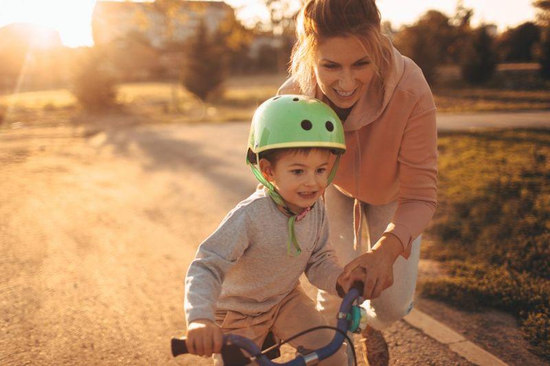 Mom helping son on bike