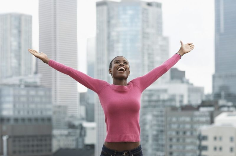 woman in city arms outstretched