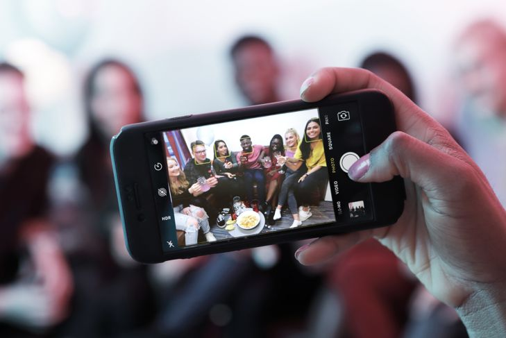 Taking photo of young people at house party