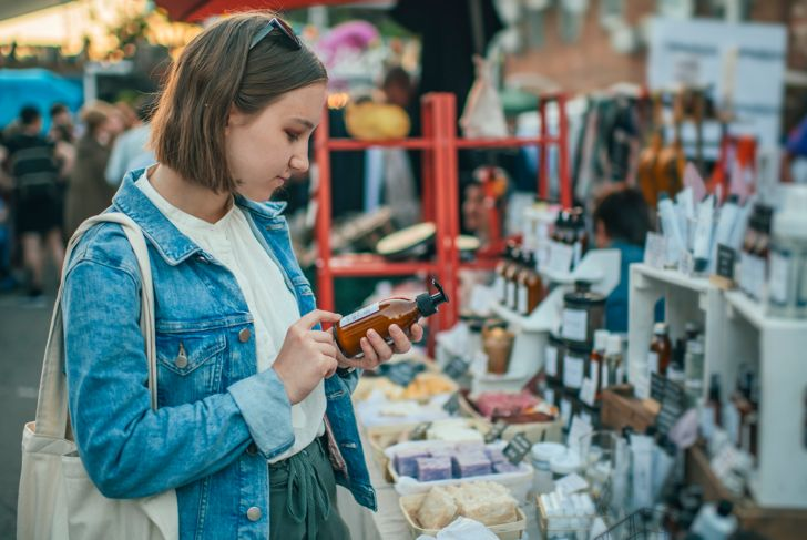 Young girl exploring organic body care goods at an open-air market with zero waste concept