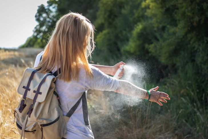 Woman tourist applying mosquito repellent on hand during hike in nature. Insect repellent.