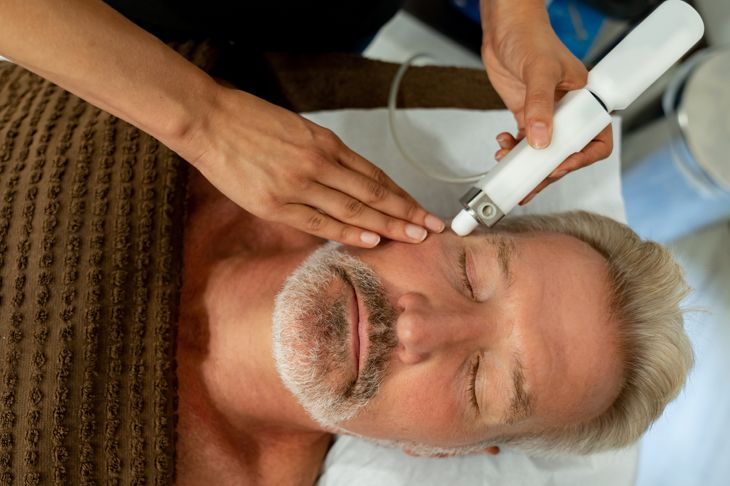 Man at the spa getting a facial laser treatment