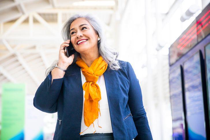 Senior Hispanic Woman using smartphone in the airport