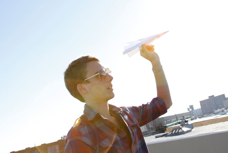 USA, New York, New York City, Brooklyn, Young man throwing paper aeroplane on roof