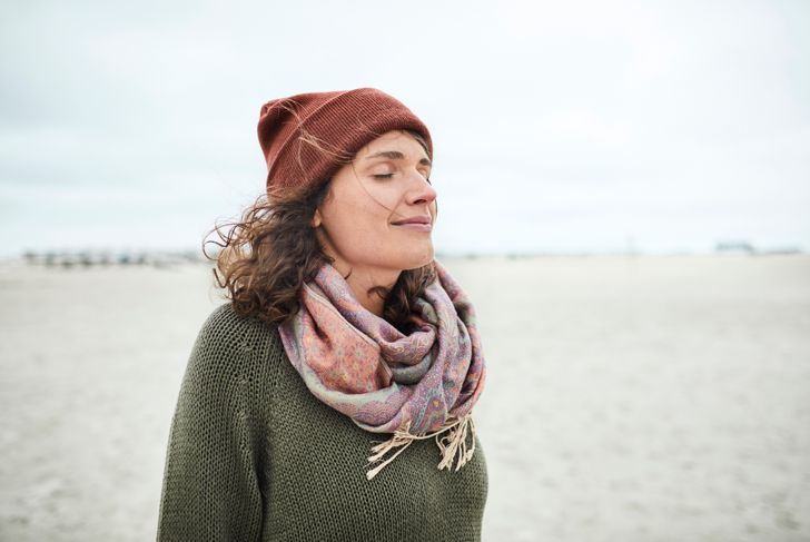 Portrait of smiling woman with closed eyes on the beach