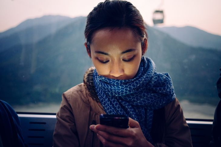 Young lady using smartphone in cable car