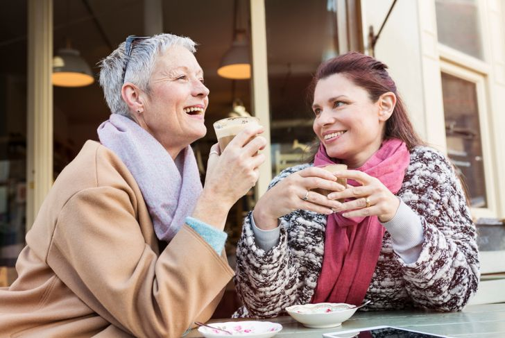 mature women meeting up for coffee in outdoor cafe