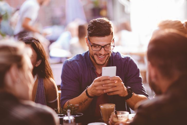 Happy hipster man at coffee shop texting on mobile phone