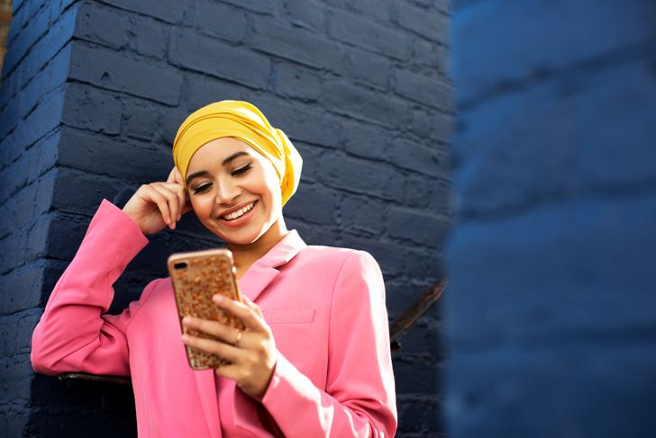 Young Muslim woman using phone