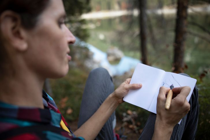 Female Hiker Writing a Journal next to the Mountain Lake - Stock Photo