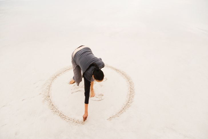 Woman drawing circle in sand on beach, elevated view