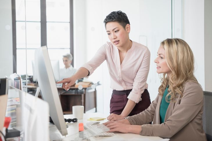 Mid adult woman using computer, young woman pointing
