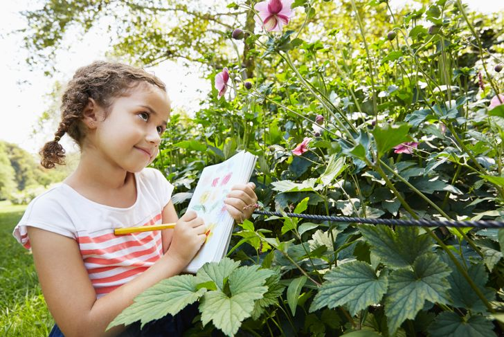 Little girl outdoors drawing flowers on notebook