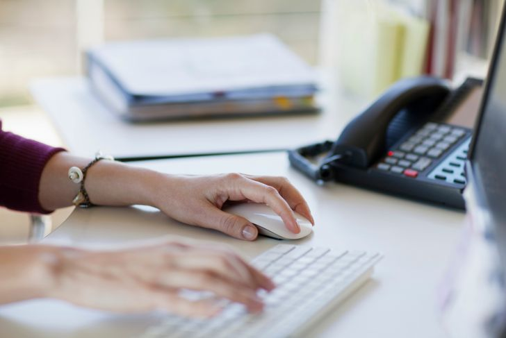 Hands of woman using computer keyboard and mouse