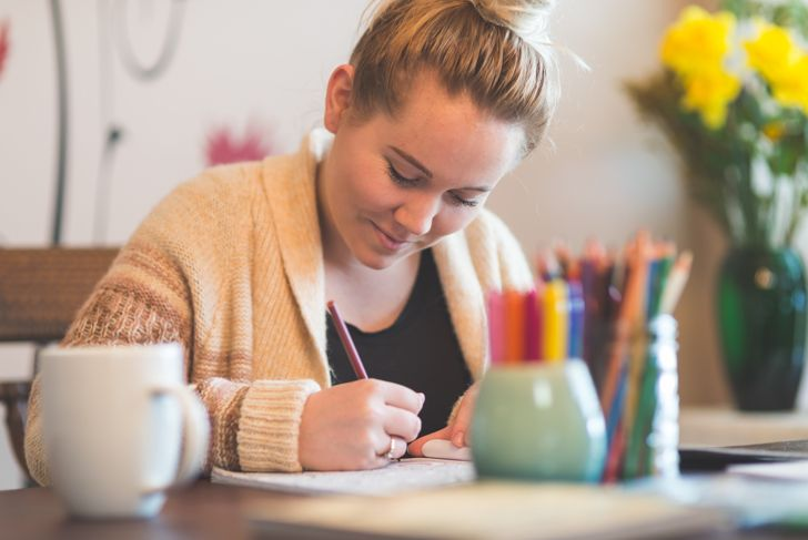 Young Woman Having Fun Using Adult Coloring Book