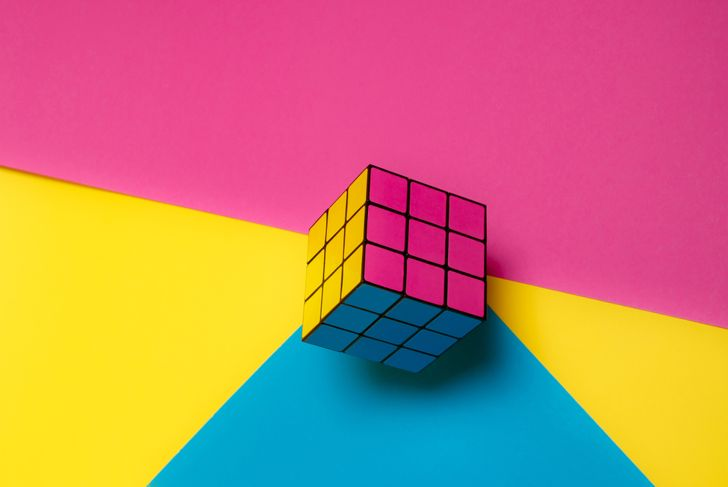 Rubik's cube on pink, yellow and blue background