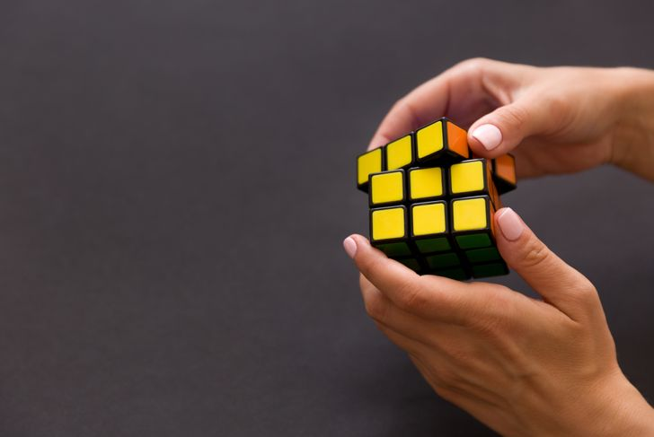 Rubik's cube in woman's hands, closeup, grey background. Girl holding Rubik's cube and playing with it.