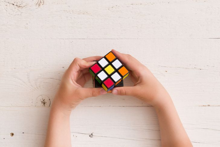 Rubik's cube in child's hands, closeup, top view, white wooden background.