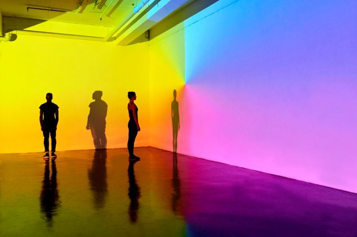 man and woman standing in a gallery space with colourful walls