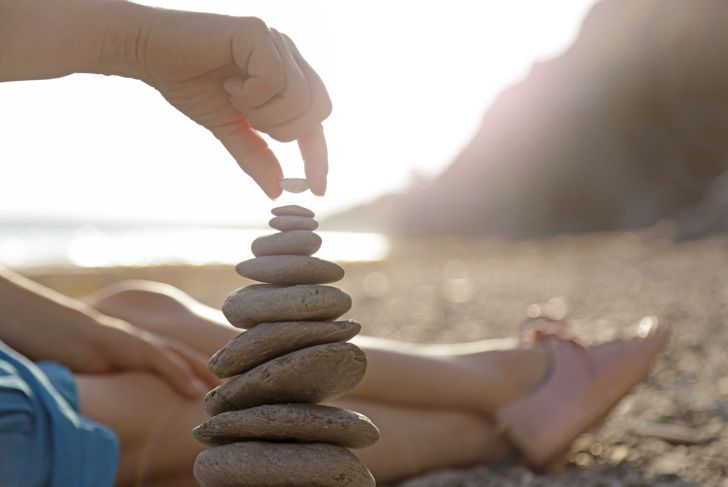 Woman stacking stones on beach