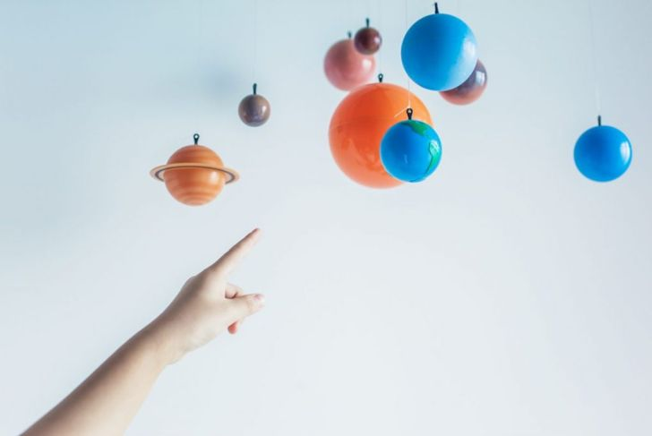 kid pointing to solar system