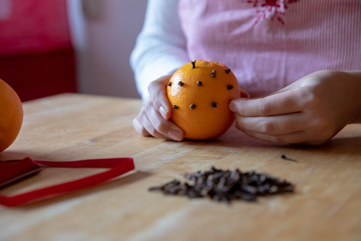 Girl putting cloves into an orange