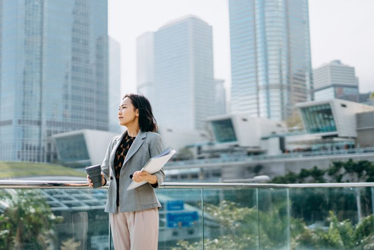 Portrait of confidence Asian businesswoman looking away and holding documents and having coffee to go against city scene in front of modern office buildings