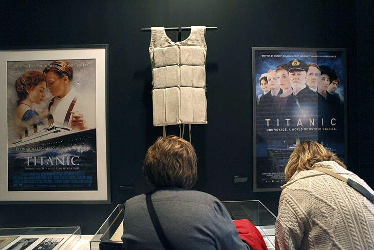 """A life vest and posters from the 1997 movie """"Titanic"""" hang on display at the opening of the """"Titanic at 100: Myth and Memory"""" exhibition on April 10, 2012 in New York City. The exhibit opened at the Melville Gallery, part of the South Street Seaport Museum, on the 100th anniversary of Titanic's launch on her maiden - and only - voyage. The exhibition features mayday communications from the ship, personal artifacts from survivors, production items from Titanic films and interactive multimedia tours through the ship. The British passenger liner sank in the North Atlantic Ocean, killing more than 1,500 people on April 15,1912 after colliding with an iceberg during her maiden voyage from Southampton, England to New York City."""