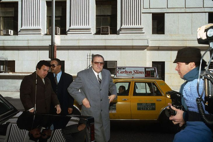 Paul Castellano is photographed February 27, 1985 outside the US Federal Courthouse in Manhattan, New York, arriving for 'The Commission trial.' To the left of Mr. Castellano (in a brown coat) is his bodyguard, confidant, and chauffeur Thomas Bilotti.