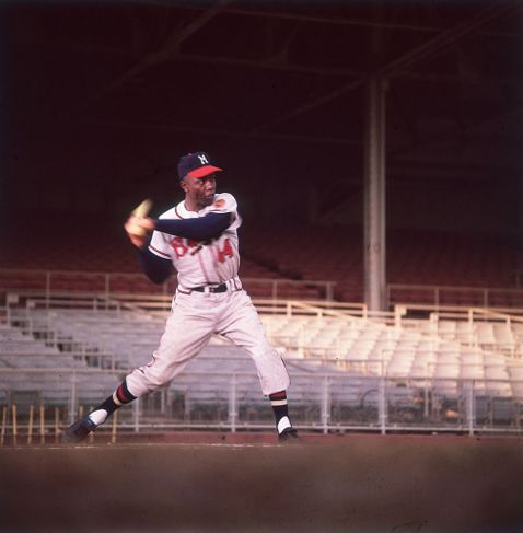 American baseball player Hank Aaron swings a bat in an empty stadium.