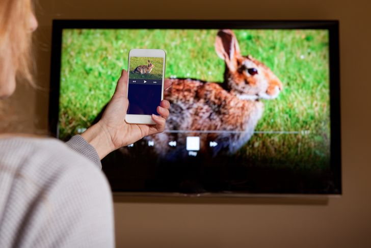 Woman Sending Video From Smartphone To TV