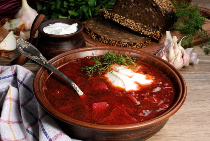 Borscht-vegetable beetroot soup, on the table with slices of rye cereal bread and sour cream