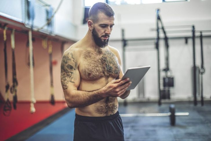 Strong man checking tablet