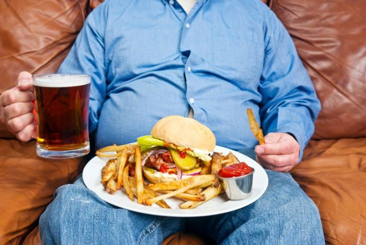 A photo of an overweight man sitting on an old couch with a very large unhealthy meal on his lap and a pint of beer in his hand. Obesity is a major cause of diabetes.