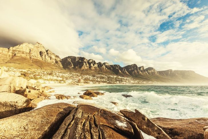 """""""View to Camps Bay during sunset, a suburb of the city of Cape Town with white sandy beaches underneath the Table Mountain. Cape Town, South Africa."""""""