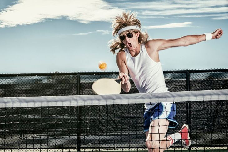 A retro 80's style guy playing pickleball on a court.