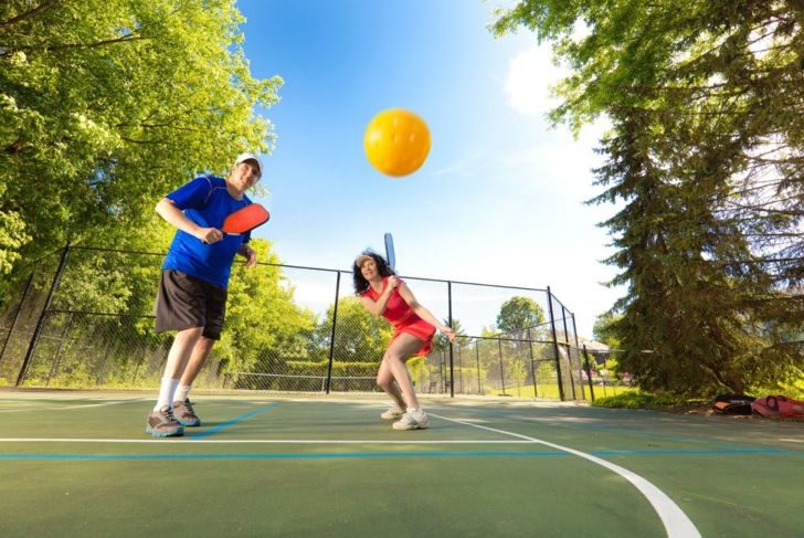 Adult Man and Woman Pickleball Player Playing Pickleball in Court