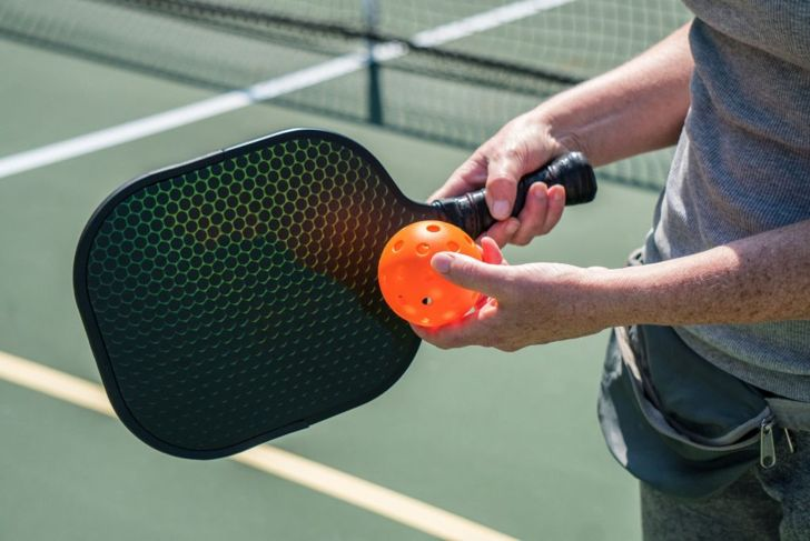 Pickle Ball paddle and ball held by player