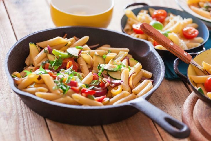 Penne pasta prepared with vegetables and parmesan cheese served in metal plate, close-up
