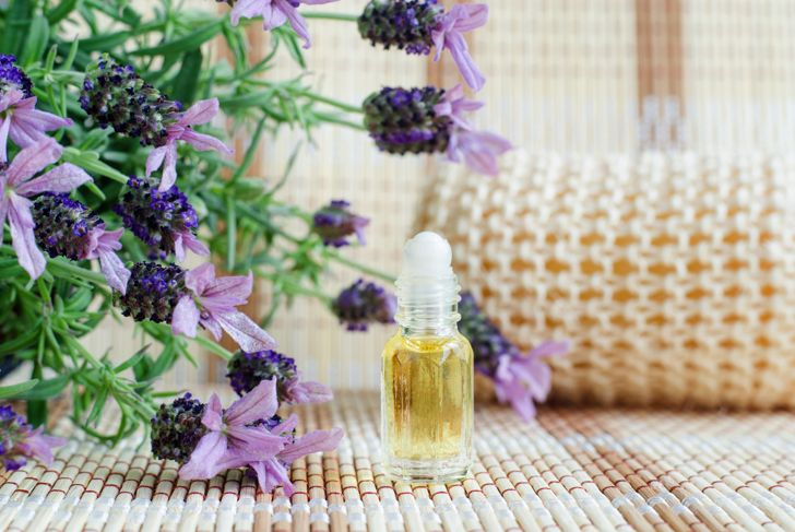 Small roll on bottle with essential lavender oil (perfume). Lavandula flowers close up. Aromatherapy, spa and herbal medicine ingredients. Copy space