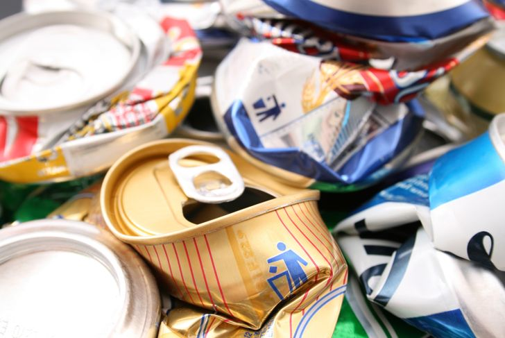 """Closeup view of crushed cans. One of them has an iconic """"throw them to the garbage can"""". Focus there."""