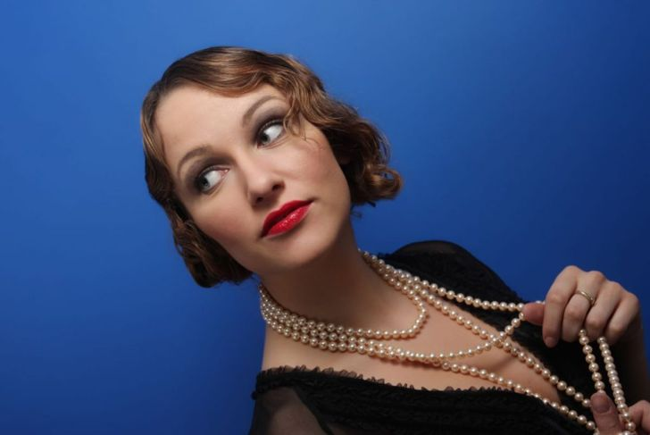 Attractive lady with nice pearls curiously looking at something