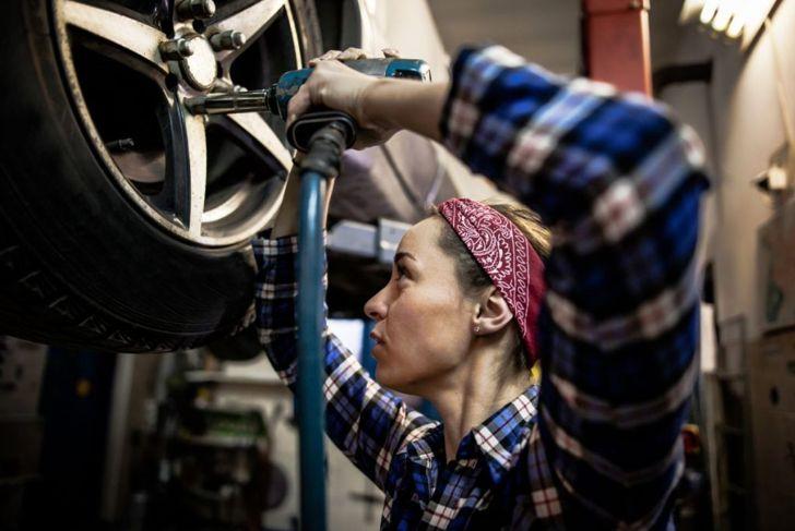 Female mechanic working on car tire service