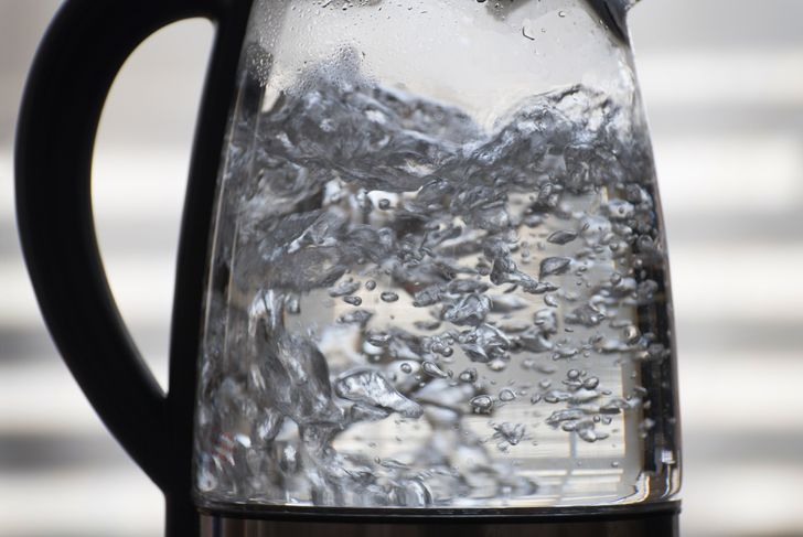 Horizontal closeup of water boiling in a glass vessel,