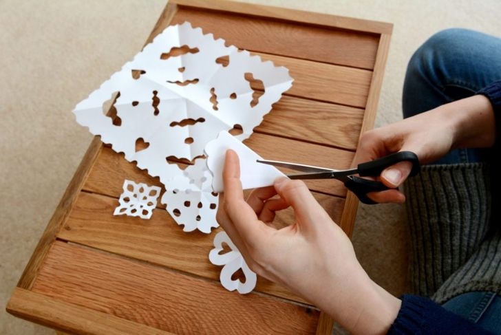 woman cutting paper snowflakes