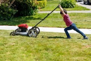 A small boy attempting to mow a lawn in a suburban neighborhood .